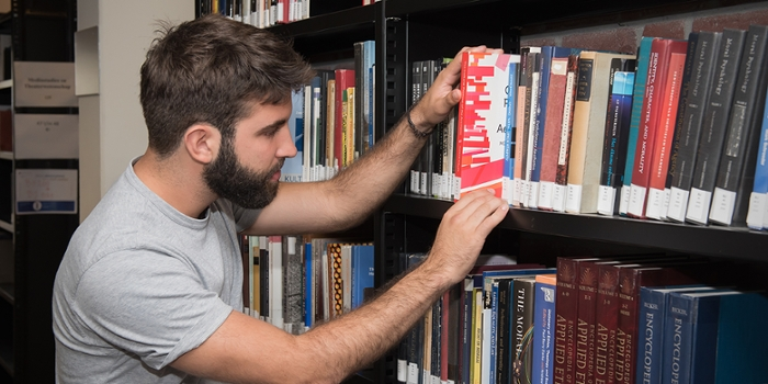 Student takes book from shelve