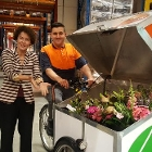 Huib de Jong and Geert ten Dam with a deliverer of  POST NL next to electrical bike loaded with flower bouquets