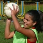 Laughing girl throwing ball during Kid Day Brazil
