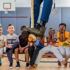 Children watching teacher climbing rope during lesson physical exercise